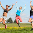 Sporty friends jumping cheerful on sunny meadow — ストック写真