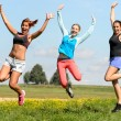 Sporty friends jumping cheerful on sunny meadow — Stockfoto