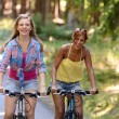 Two teenage girls riding their bikes — Stock Photo