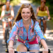 Teenage girl riding bike with friends — Stock Photo
