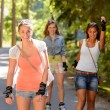 Three women friends roller skating outdoors — Stock Photo