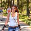 Young woman roller skating outdoors summer sport — Stock Photo