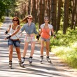 Three friends on in-line skates outdoor — Stock Photo