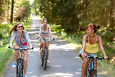 Happy girls riding bicycles outside — Stock Photo