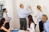 Colleagues Discussing Strategy On Whiteboard — Stock Photo