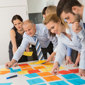 Business Colleagues Arranging Labels On Table — Stock Photo