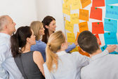 Collega's brainstormen voor whiteboard — Stockfoto