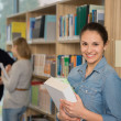 Student holding books in university library — Stock Photo #44731679