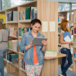 College student using tablet in library — Stock Photo #44731685