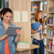 University student looking at tablet in library — Stock Photo #44731691
