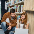 Friends studying together on laptop in library — Stock Photo