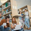 Classmates studying together on laptop in library — Stok fotoğraf