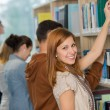Student choosing book from bookshelf in library — Stock Photo