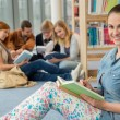 Smiling girl in university library — Stock Photo