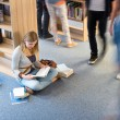 Student sitting floor in library blur motion — Stock Photo