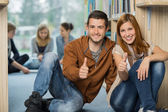 Happy students showing thumb up in library — Stock Photo