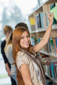 Student taking book from bookshelf in library — Stock Photo