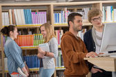 Group of students discussing in library — Stock Photo