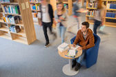 Student writing notes in library blur motion — Stock Photo