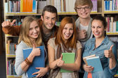 Friends showing thumb up in library — Stock Photo