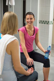 Woman smiling at friend in locker room — Stok fotoğraf