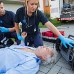 Paramedics checking pulse of man — Stock Photo