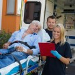 Emergency team treating patient on stretcher — Stock Photo