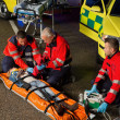 Paramedics assisting motorbike driver on stretcher — Stock Photo #46253439