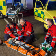 Paramedics helping motorbike driver on stretcher — Stock Photo #46253449