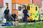 Paramedical team arriving to unconscious man — Zdjęcie stockowe