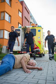 Emergency team assisting unconscious man — Stock Photo
