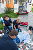 Paramedics treating injured man — Stock Photo
