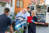Emergency team assisting injured man — Stock Photo