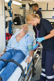 Paramedical team examining patient on stretcher — Stock Photo
