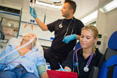 Paramedical team treating man in ambulance — Stock Photo