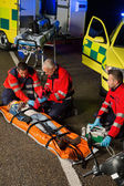 Paramedics assisting motorbike driver on stretcher — Stock Photo