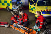 Paramedics helping motorbike driver on stretcher — Stock Photo