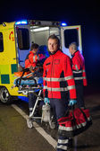 Paramedic with team assisting injured patient — Stock Photo