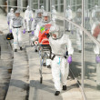 Biohazard medical team walking to building — Stock Photo #46796461