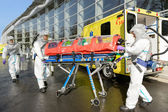 HAZMAT medical team pushing stretcher — Stock Photo