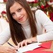 Young woman thinking while writing Christmas card — Stock Photo #4695755