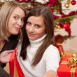 Two young women in front of Christmas tree — Stock Photo #4695770