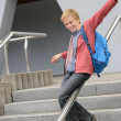 Student sliding down railing on stairway — Stock Photo #47138741