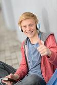 подростковая студент палец вверх слушать музыку — Стоковое фото