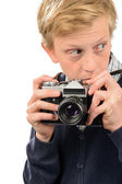 Suspicious teenage boy holding retro camera — Stock Photo