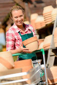 Woman putting pots in cart — Stock Photo