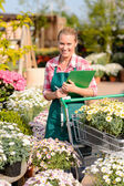 Woman put flowers in cart — Stock Photo