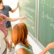 Students write on green chalkboard — Stock Photo #48611127