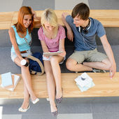 Three college students looking tablet — Stock Photo