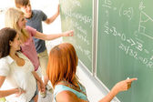 Students write on green chalkboard — Foto Stock